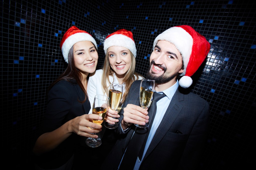 Group of cheerful business people in Santa caps toasting with ch